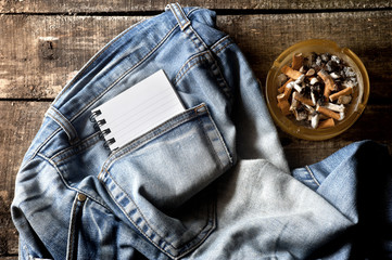 Pair of dirty jeans,notepad and an ashtray