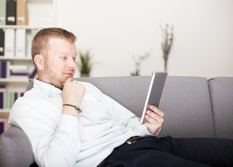 Thoughtful man reading his tablet computer
