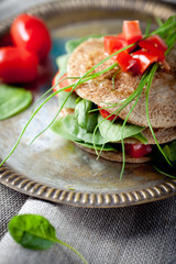 Wholegrain flat bread with spinach and tomatoes