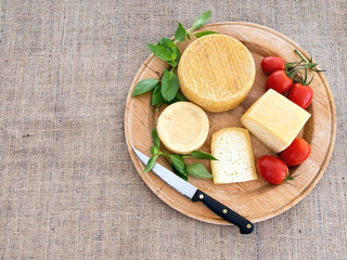 Cheeseboard with rustic cheeses and tomatoes, on hessian.
