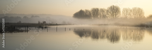 Panorama landscape of lake in mist with sun glow at sunrise - 70215001