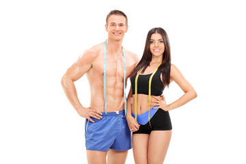 Male and female athletes with measuring tapes