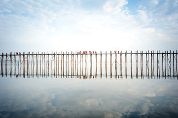 U bein bridge in Myanmar with many Buddhist monks crossing it at