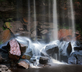 Wet rocks and small waterfall landscape background