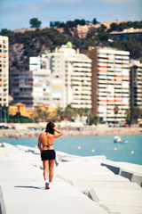 Young woman walking at the border of the coast, during sport ses