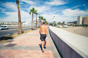 Senior man walking on promenade at coast