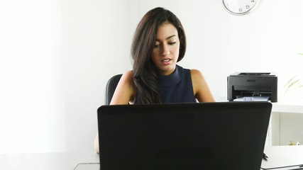 cheerful young woman in office, working with laptop computer