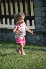 Bambina che corre sul prato