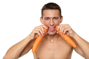Young athletic man shows carrots holding in hands