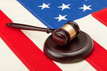 Judge gavel and soundboard laying over USA flag - closeup shot