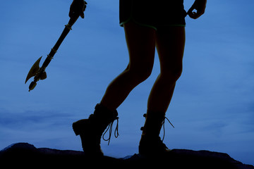 silhouette woman legs hatchet behind