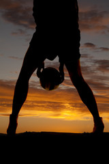 silhouette woman legs hold ball between legs