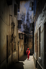 Veiled woman walking through a narrow street