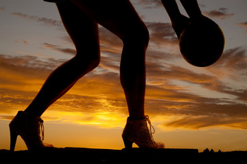 silhouette woman legs hold ball to side