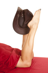 woman legs under red sheet with brown hat on one foot