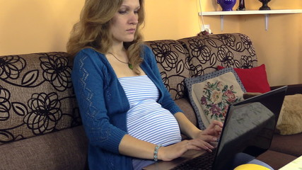 Pregnant serious woman using laptop computer at home