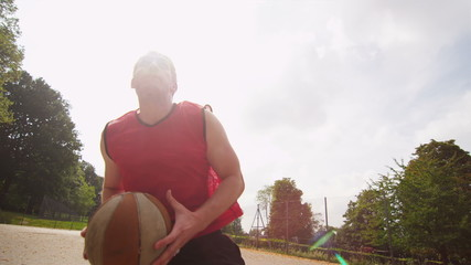 Basketball player dunking on an outdoor court in slow motion