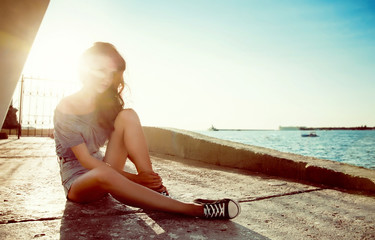 young beautiful smiling girl on a background of sea and sun