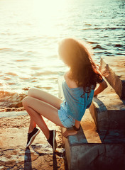 young beautiful  girl on a background of sea and sun