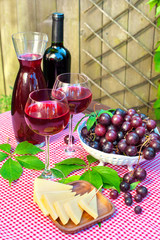 Two glasses of delicious homemade semisweet  red wine with grape