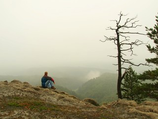 Tourist sit  on peak of sandstone rock and watching over gulch