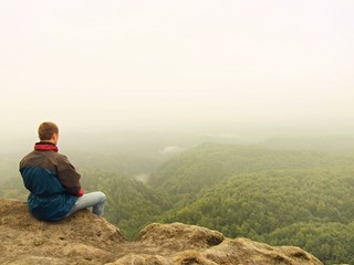 Sad man sit  on the peak of sandstone rock and watching down