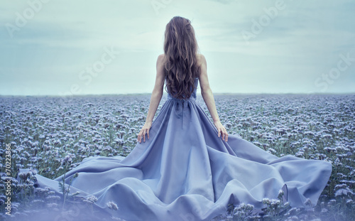 Back view of standing young woman in blue dress