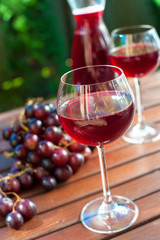 Two glasses of delicious homemade red wine with grape