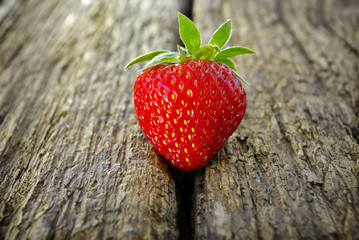 Ripe red strawberry on a wooden background