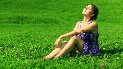 Happy woman sitting on the meadow and enjoying sunlight
