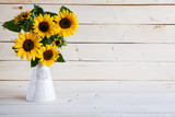 Sunflowers in a vase on a rustic, gray background