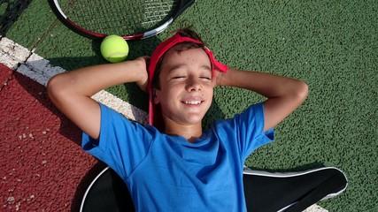 Niño tumbado junto a raqueta de tenis