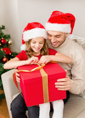 smiling father and daughter opening gift box