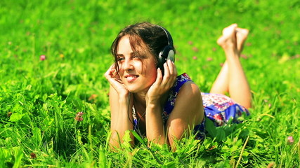 Woman lying on the meadow and  listening music on headphones