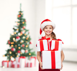 girl in santa helper hat with many gift boxes