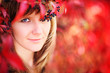 Young woman autumn portrait in crown of red autumn leaves