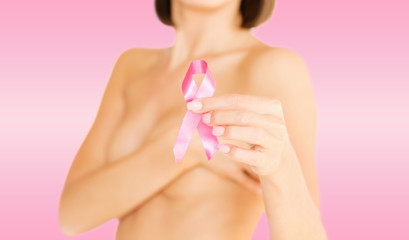 hand holding pink breast cancer awareness ribbon