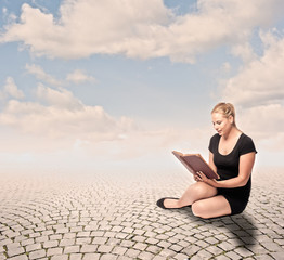 young woman reading a book on cobblestone background