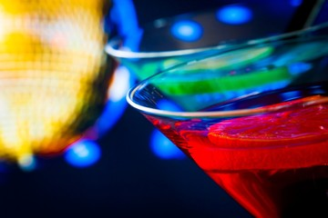 detail of red cocktail with gold sparkling disco ball background