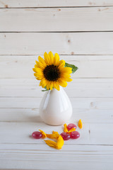 sunflower on a wooden background with red candy
