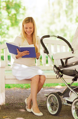 happy mother with book and stroller in park