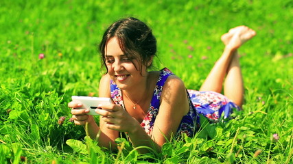 Happy girl lying on green meadow and typing on cellphone