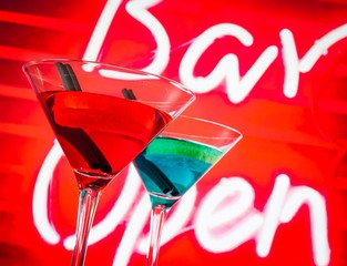 blue and red cocktail with neon bar word background