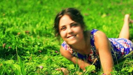 Woman rolling on green meadow and smiling to the camera