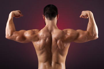 Young bodybuilder showing his back muscles on a dark background