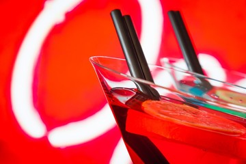 detail of red cocktail with neon background with space for text