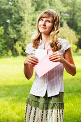 Young caucasian woman holding a blank letter in pink envelope