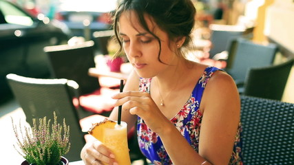Pretty girl drinking cocktail with pineapple and smiling