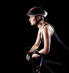 side view of a cyclist girl on black background
