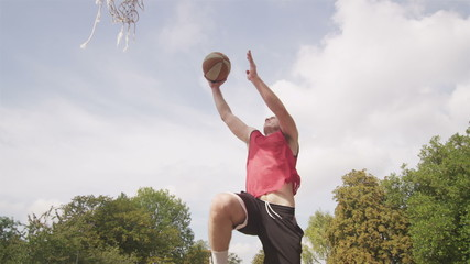 Basketball player slam dunking in slow motion